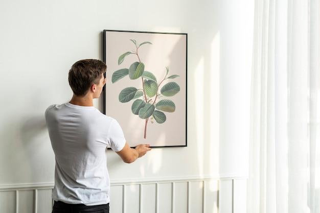 Vintage blad schilderij wordt opgehangen door een jonge man aan een witte minimale muur