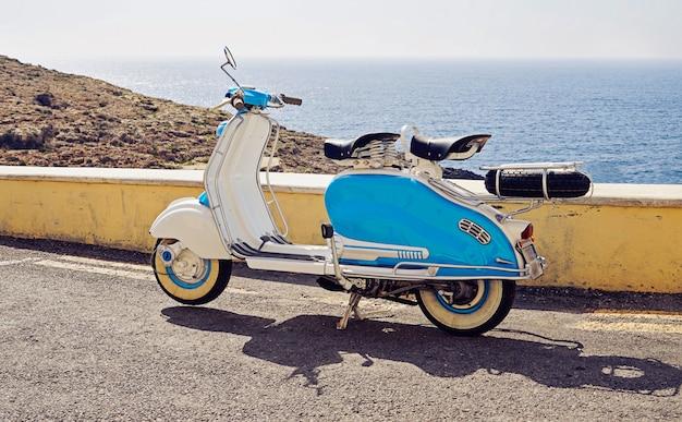 Vintage blauw-witte tweezitter scooter geparkeerd op straat