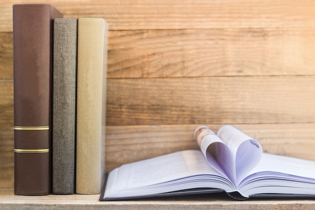 Vintage boeken en open boek op houten plank