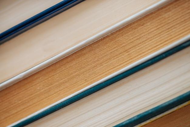 Vintage boekenclose-up. stapel gebruikte oude literatuur in schoolbibliotheek. achtergrond van oude chaotische lectuur. stoffige verschoten boeken diagonaal met copyspace. oude boekhandel.