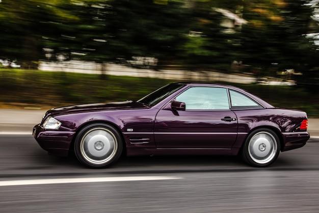 Vintage bordeaux sedan auto rijden op de weg, zijaanzicht.