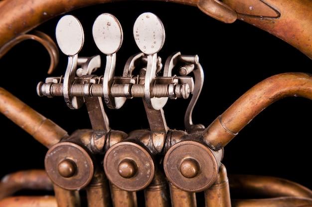 Vintage bronzen pijpen, klep, belangrijke mechanische elementen franse hoorn op zwarte geïsoleerde achtergrond.