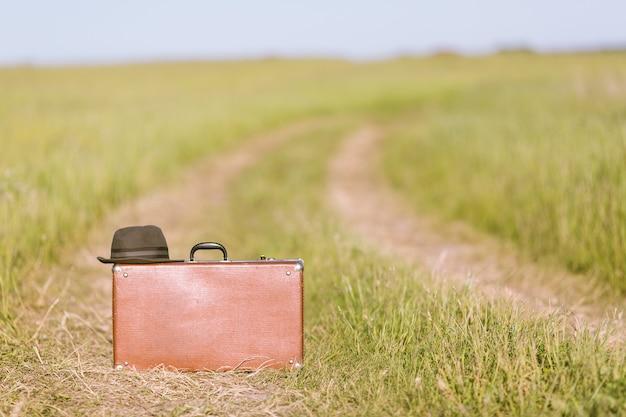 Vintage bruine koffer en hoed op de weg in het groene veld.
