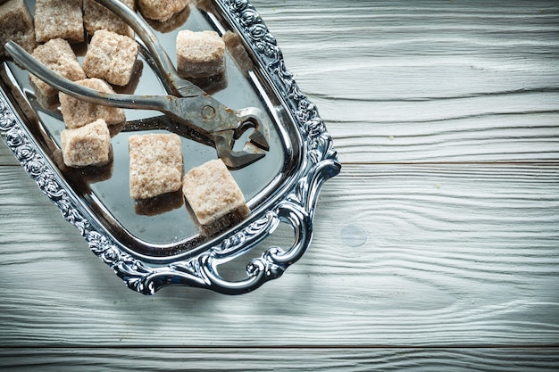 Vintage bruine suiker tang dienblad op houten bord