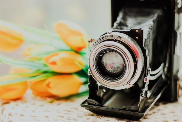 Vintage camera met mooi boeket bloemen op gebreide tafellaken.