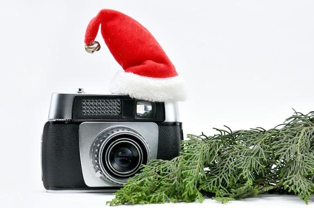 Vintage camera omgeven door kerstboom en speelgoed op geïsoleerde witte ruimte