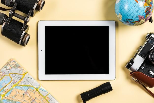 Vintage camera; verrekijker; wereldbol; kaart; flitslicht dichtbij de digitale tablet op beige achtergrond