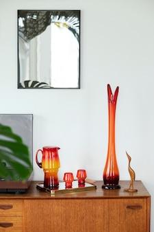 Vintage compositie op de houten kast met retro rode vaas, vinylrecorder, spiegel en elegante persoonlijke accessoires. sjabloon.