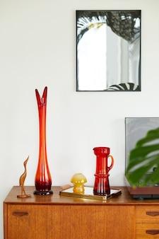 Vintage compositie op de houten kast met retro rode vaas, vinylrecorder, spiegelmodel en elegante persoonlijke accessoires. sjabloon.