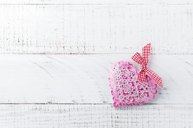 Vintage decoratieve hartvormige decoratie op een houten standaard op een witte achtergrond