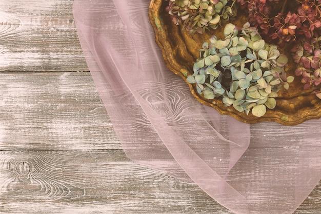 Vintage dienblad met gedroogde blauwe hortensia bloemen op een paarse transparante tule stof op een grijze tafel. vlakke stijl