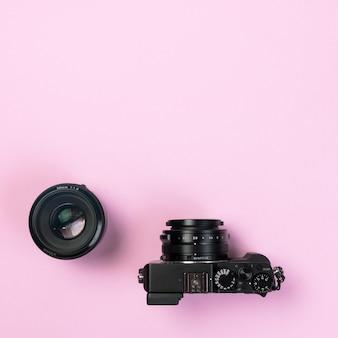 Vintage digitale compactcamera en lens 50 mm op roze pastelkleurenachtergrond