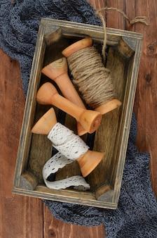 Vintage doos met klossen, spoelen, spoelen, draden en kant. kleine doos met tools in houten werkplaats