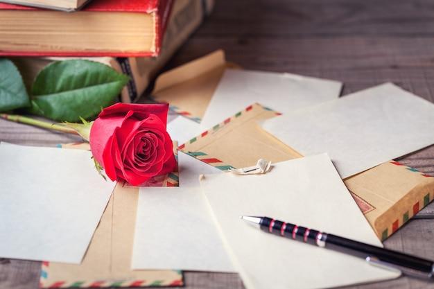 Vintage enveloppen, rode roos en vellen papier verspreid over houten tafel voor het schrijven van romantische brieven.