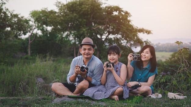 Vintage familie van fotografen maakt graag foto's met de filmcamera in de groene natuur en de prachtige zonsondergang