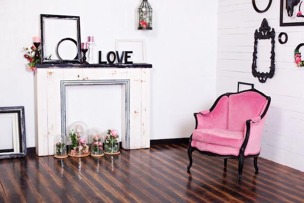 Vintage fauteuil van velours, in een lichte kamer en een kunstmatige open haard. interieur zolder met houten witte muren. fotolijsten aan de muur. kamer in gotische stijl.