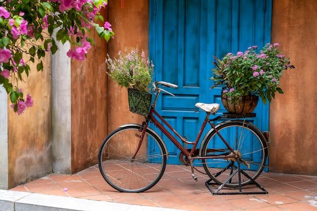 Vintage fiets met mand vol bloemen naast een oud gebouw in danang