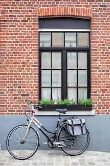 Vintage fiets met tas bij het raam in brugge