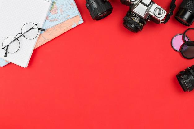 Vintage filmcamera, diverse lenzen, bril, notebook en kaart