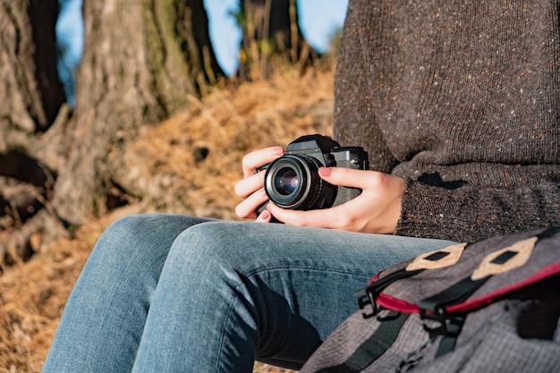 Vintage filmcamera in vrouwelijke handen. close-up shot van een vrouw met filmcamera buitenshuis