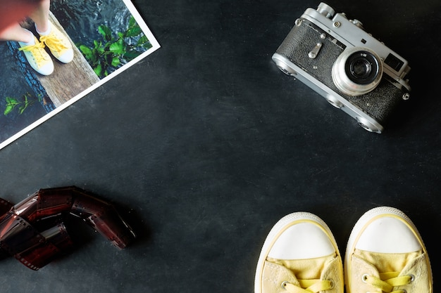 Vintage fineart filmfotografie set gele sneakers, vintage camera, film en fotoprint op zwarte achtergrond