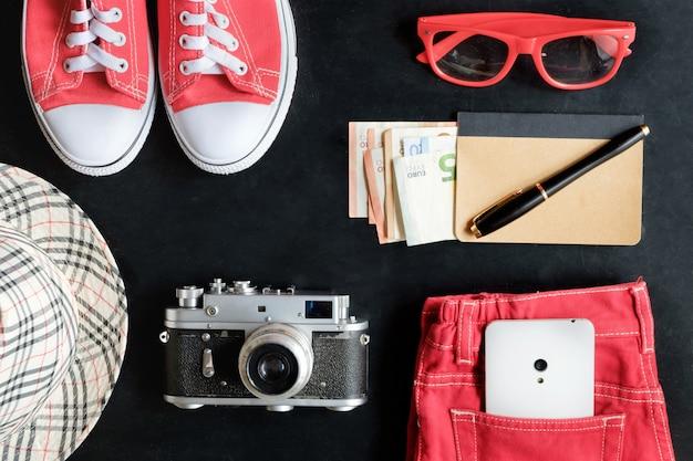 Vintage fineart filmfotografie set rode sneakers, rode bril, rode spijkerbroek, vintage camera, witte telefoon, notebook en geld, stylus pen, geruite hoed