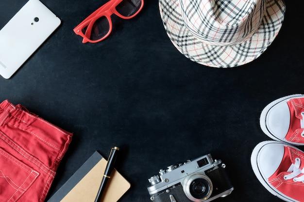 Vintage fineart filmfotografie set rode sneakers, rode bril, rode spijkerbroek, vintage camera, witte telefoon, notebook, stylus pen, geruite hoed