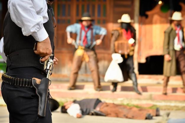 Vintage foto's van een sheriff en een groep cowboyrovers die oog in oog een bank beroven. iedereen heeft een pistool in de hand, focus op de sheriff.
