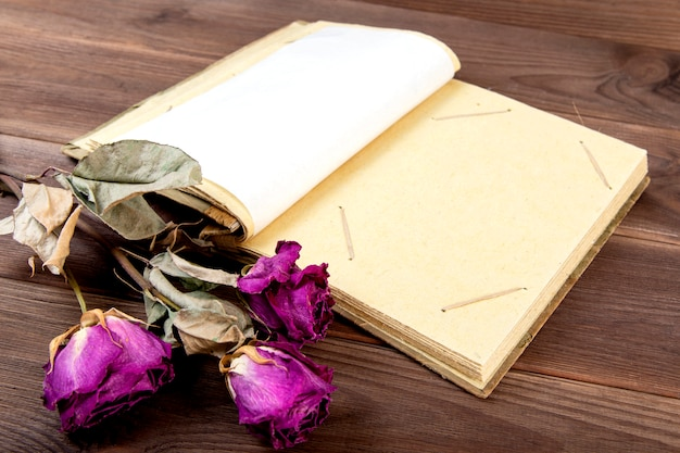 Vintage fotoalbum op hout met droge bloemen.