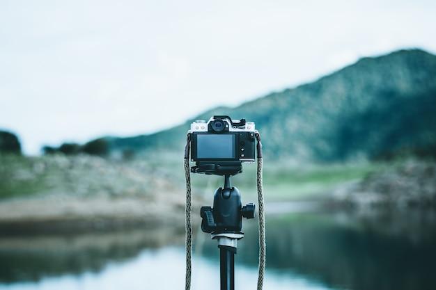 Vintage fotocamera staat op statief in het rustige bos.