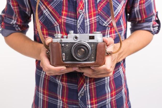Vintage, fotograaf en hobby concept - close-up van retro camera in iemands handen over de witte achtergrond