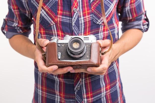 Vintage, fotograaf en hobby concept - close-up van retro camera in man handen over het wit