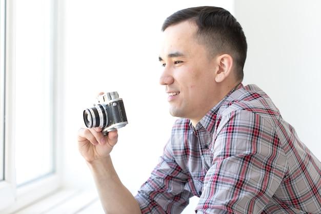Vintage, fotograaf en mensen concept - knappe aziatische man met retro camera binnenshuis