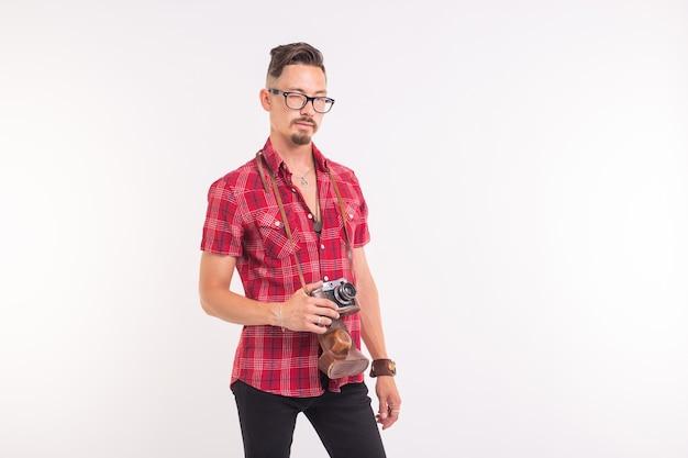 Vintage, fotograaf en mensen concept - knappe man met retro camera op witte achtergrond met kopie ruimte.
