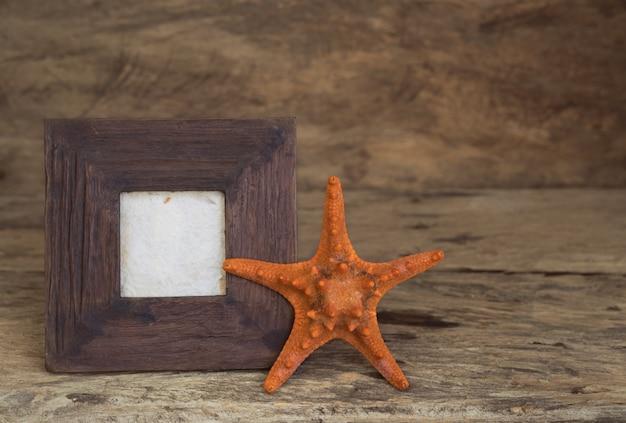 Vintage fotolijst met zeesterren op houten tafelblad achtergrond