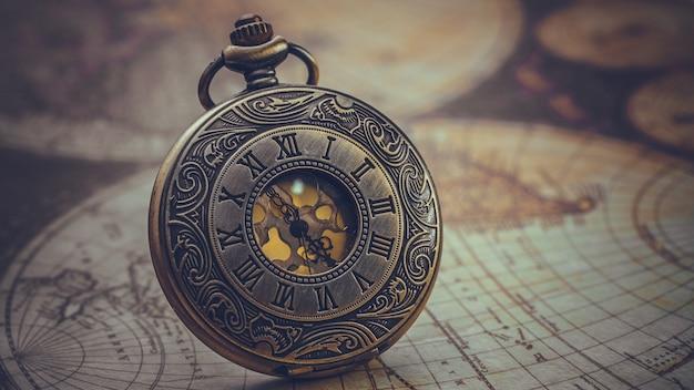 Vintage gegraveerde metalen horloge gezicht hanger ketting op oude wereldkaart