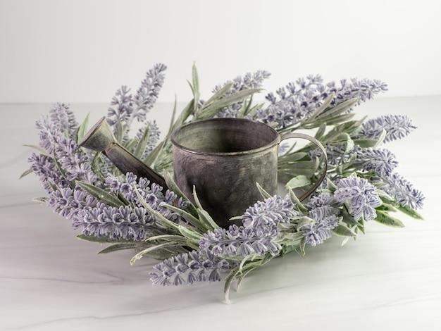 Vintage gieter versierd met paarse lavendel tegen een grijze ondergrond