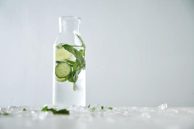Vintage glazen fles gevuld met koude verse komkommer, munt en limoen limonade zoals mojito zonder alcohol