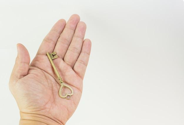 Vintage gouden sleutel in de hand close-up beeld.