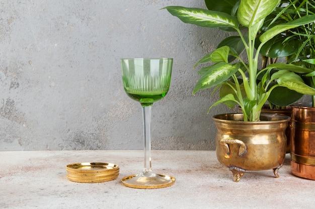 Vintage groene wijnglas gouden onderzetters en planten