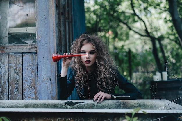 Vintage heks voert magisch ritueel uit, met elixer in de hand aan de vooravond van halloween