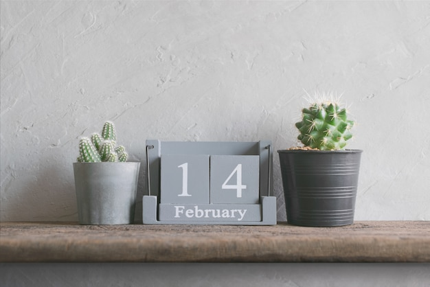 Vintage houten kalender voor 14 februari op houten tafel