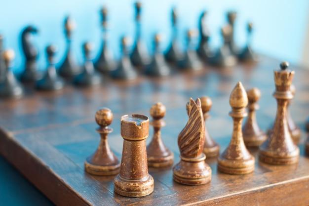 Vintage houten schaakstukken op een oud schaakbord.