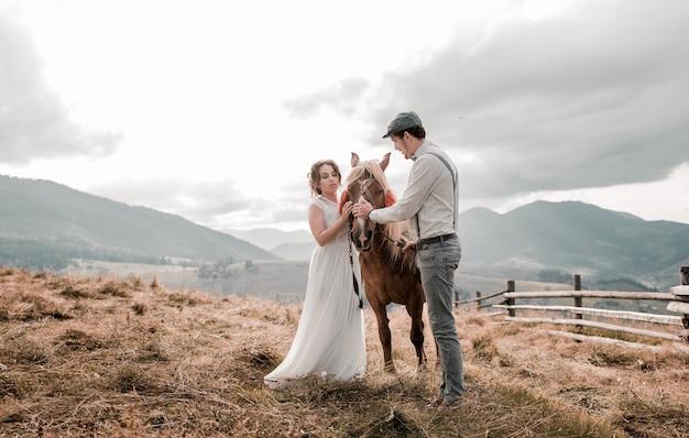 Vintage huwelijk van bruid en bruidegom op een boerderij met een paard op piekheuvels