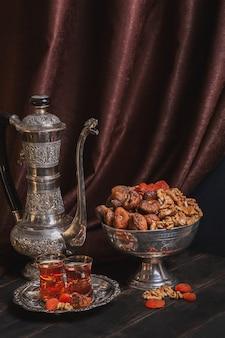Vintage kan voor water of thee, een vaas met gedroogd fruit en een bord met thee in armuda glazen.