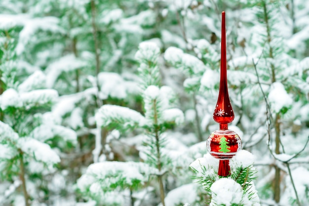 Vintage kerstboomtopper op een levendige spar in besneeuwd winterbos buiten