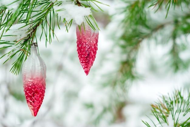 Vintage kerstversiering op een levendige spar in besneeuwd winterbos buiten