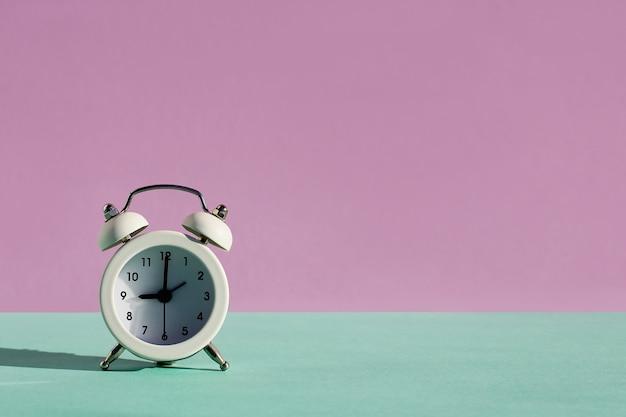 Vintage klassieke witte wekker, minimalistische designbel op violetblauwe pastelachtergrond. rusturen tijd van het leven, goedemorgen, wakker wakker concept