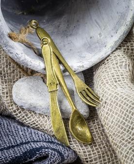 Vintage klein bestek met een handdoek en een aarden pot