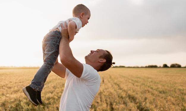 Vintage kleurenfoto gelukkig vreugdevolle vader plezier werpt in de lucht jongetje kind, familie, reizen, vakantie, vaderdag